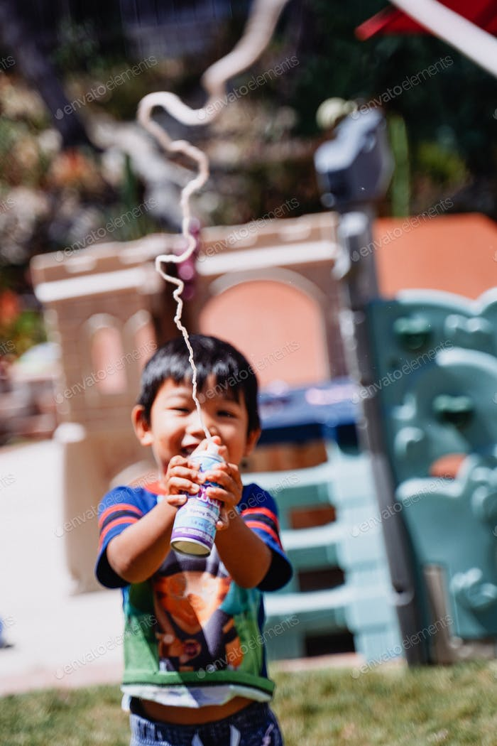 Diverse young happy smiling little boy playing with silly string at home backyard outdoor outside