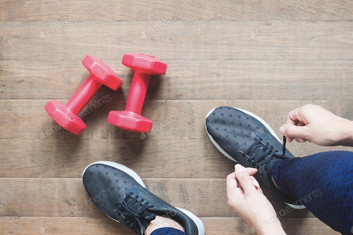 Tying sport shoes, Asian woman getting ready for weight training