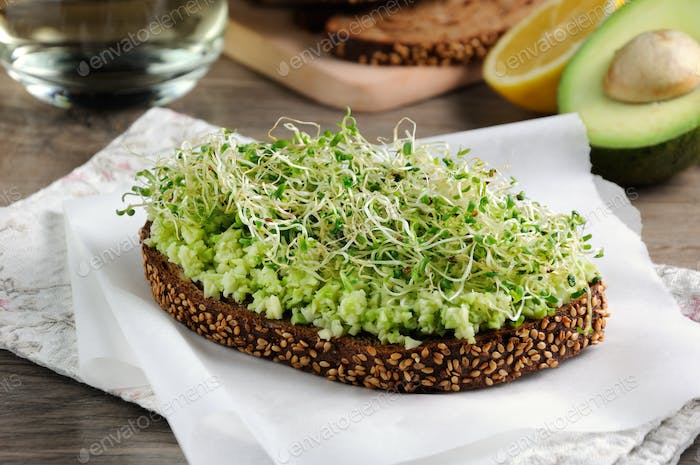 Sandwich of tender, juicy germinated alfalfa and avocado sprouts on slices of rye bread with cereals