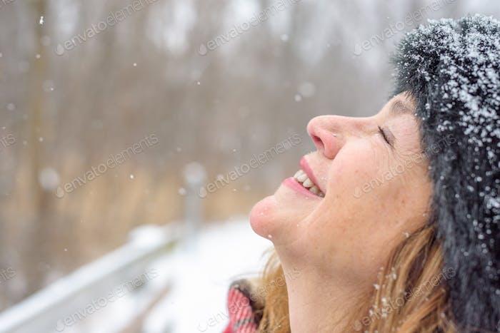 Schneeflocken fallen sanft auf das Gesicht der Frau