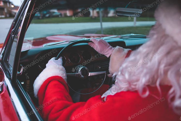 Santa Claus driving a classic red American muscle car