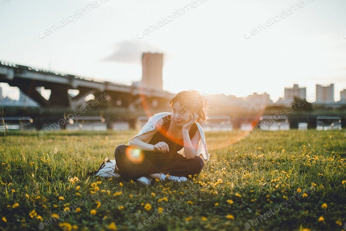 portrait of a girl sitting on grass at the park with the sunflare