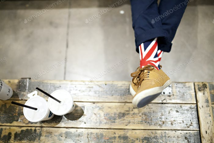man wearing union jack socks resting feet on coffee table
