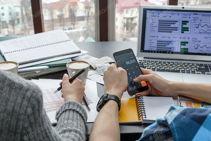 young people at their desk make financial calculations