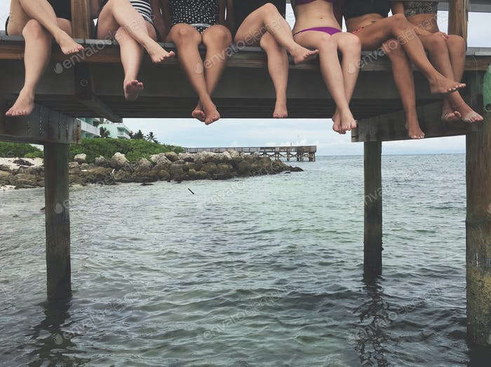 Young women sitting on pier