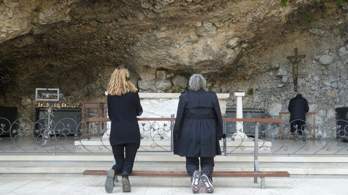 Rear view of people praying at place of worship
