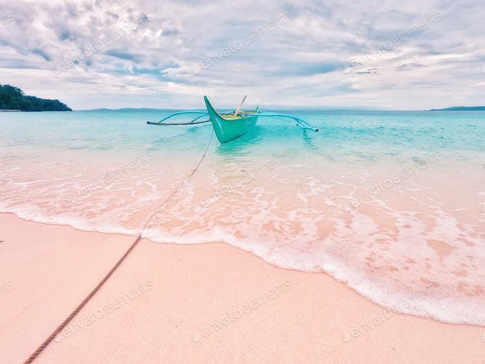 Cloudy summer. Light pink sand and turquoise blue sea water of Subic Beach.
