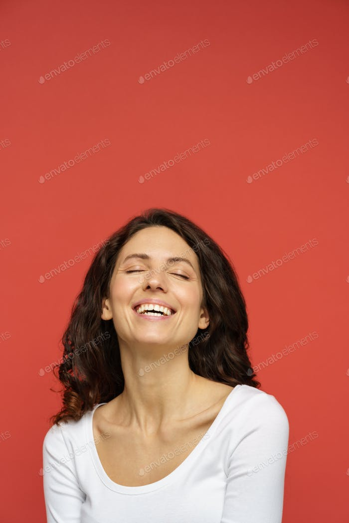 Portrait of carefree female in 30s with closed eyes, perfect skin, white smile on red background