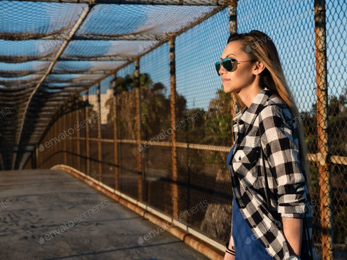 Young woman standing on street bridge urban outdoor looking at sun fence gate downtown city fashion