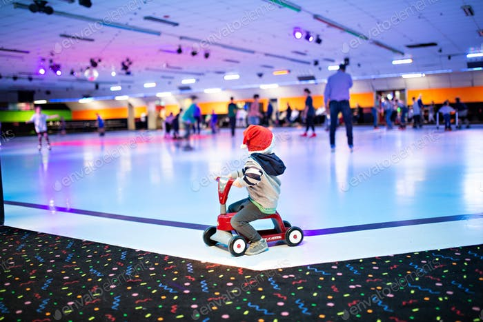 boy riding a scooter at a skating rink