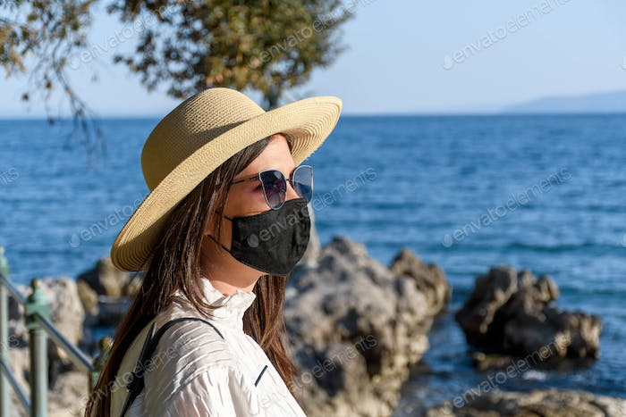 Side view of young woman with black face mask standing on shore of sea in spring, summer.