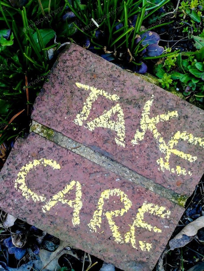 Tenga cuidado palabras en la naturaleza en ladrillos en la naturaleza estímulo para todas las personas durante el Coronavirus