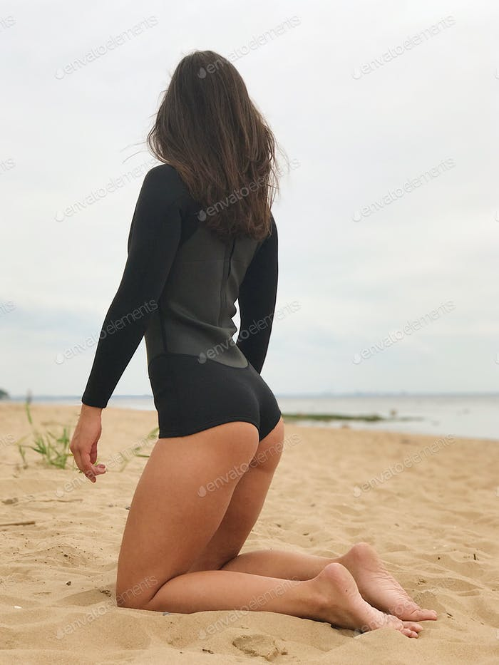 Woman from behind, sitting on the beach in a black wetsuit, sea background