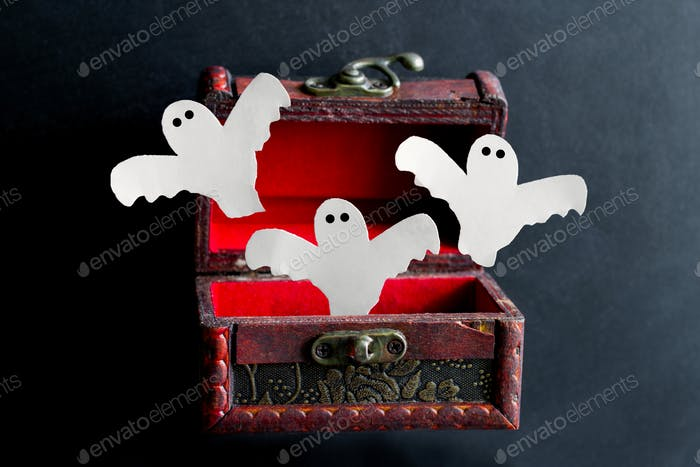 paper cut scary ghosts fly out of an old vintage  wooden chest on a black background