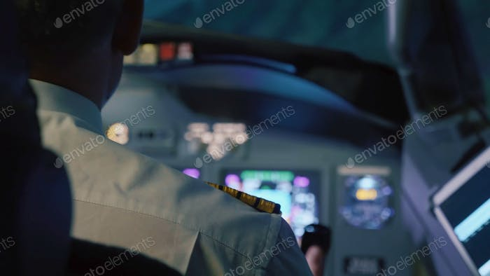 Captain is controls the airplane at night, rear view. Pilot in cockpit of passenger airliner