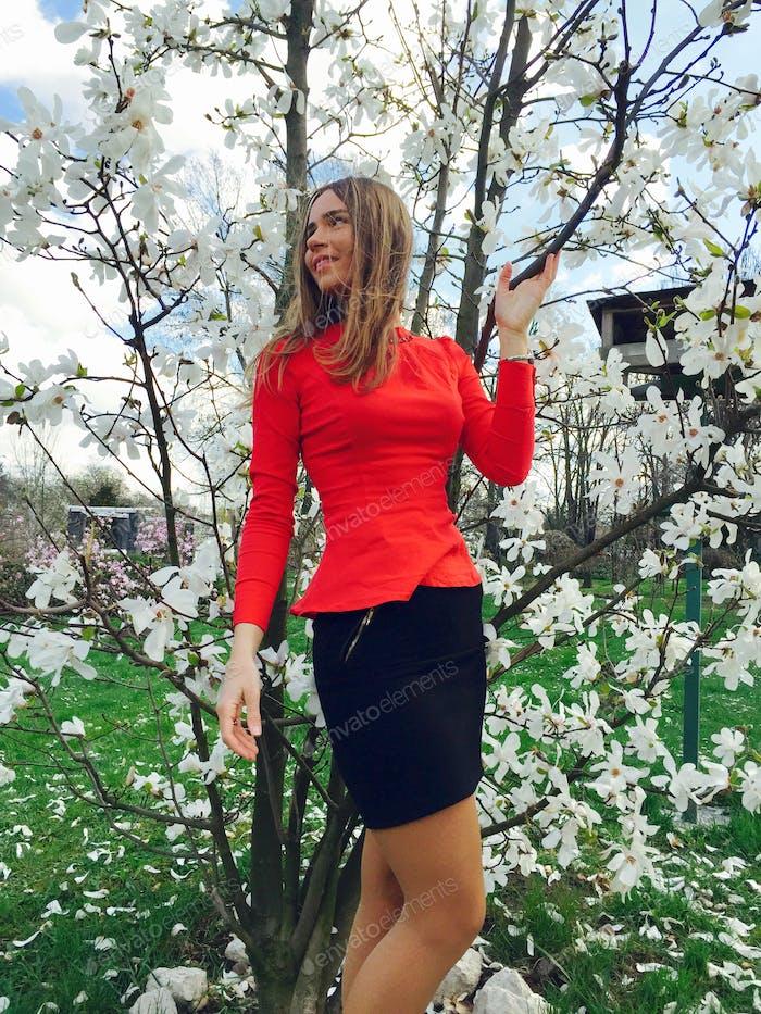 Frau professionell in der Nähe von Magnolie Baum im Frühjahr gekleidet