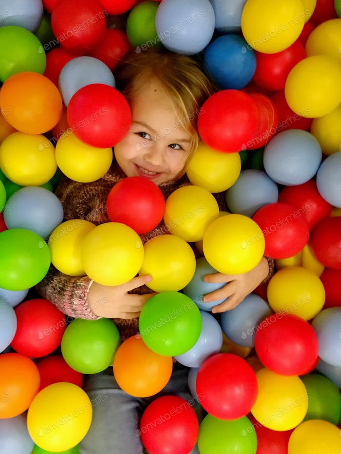 Child buried in colourful play land balls