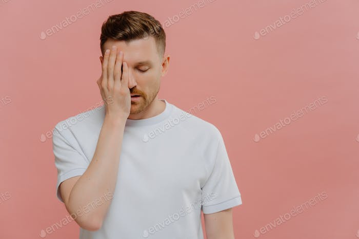Serious tired man makes face palm feels bored spending time alone covers eye with hand