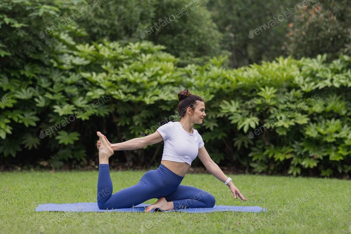 happy young sporty yoga coach teacher lying on mat and exercising outdoor in summer park at morning