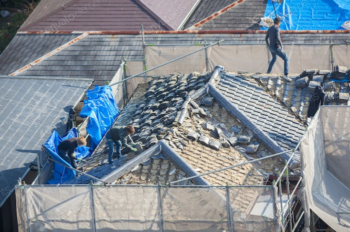 People working to tile a roof damaged by natural disaster