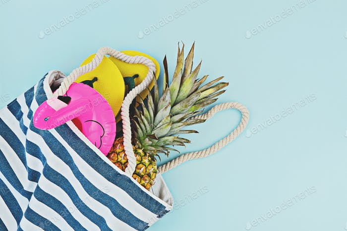 Colorful summer pool or beach set flat lay. Floated inflatable flamingo, flip-flops, pineapple over