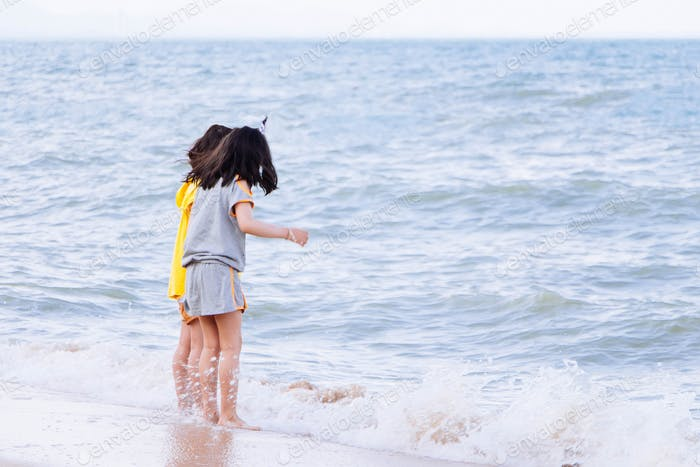 The girl is walking on the beach happily.