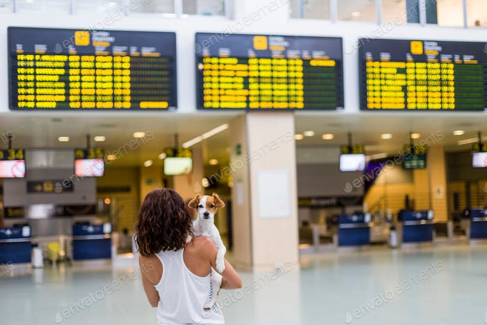 young woman at the airport ready to travel with her dog