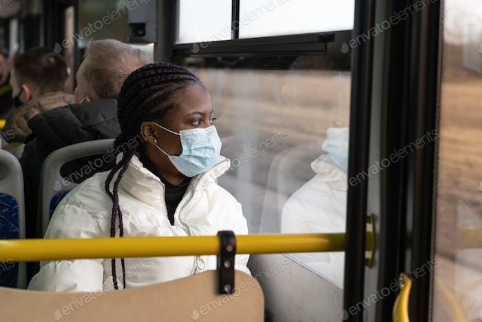 Afroamerikanerin trägt medizinische Maske, Reisen in öffentlichen Verkehrsmitteln, Bus in neuer Normalität von Covid