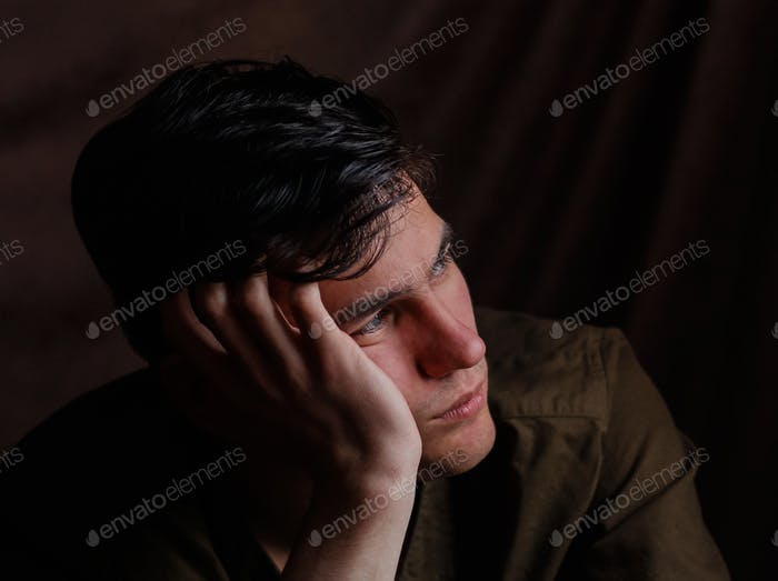 Serious sad young man thinking about problem. Depression and anxiety disorder concept