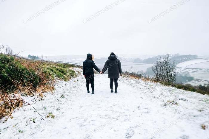 Girls holding hands walking in the snow in Yorkshire United Kingdom