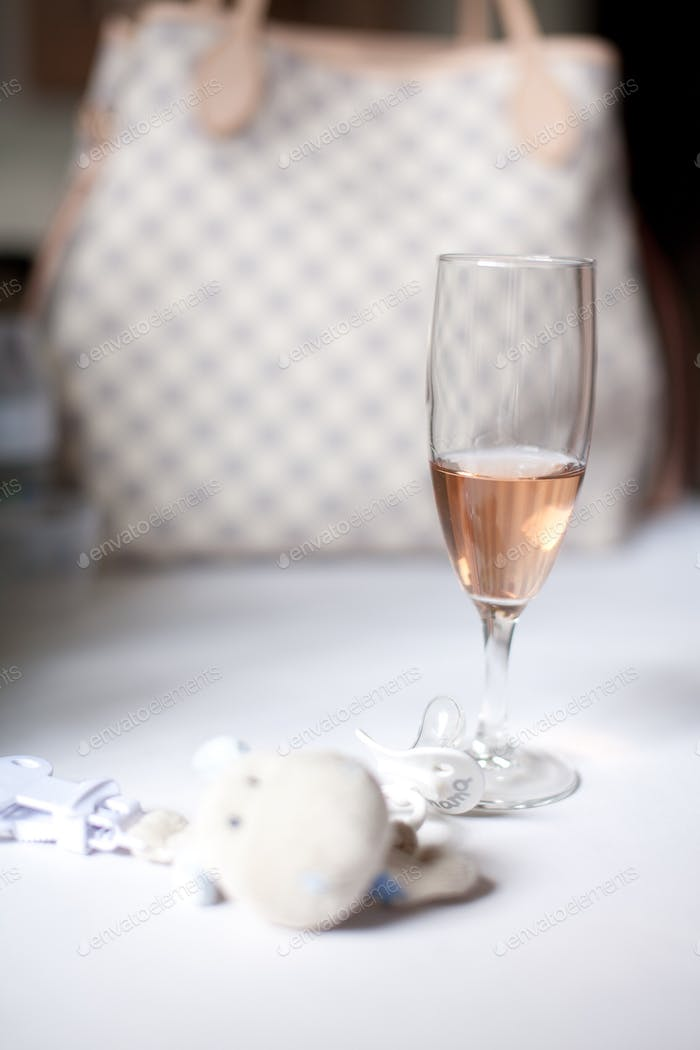 Baby pacifier and cuddly toy and a glass of rose champagne in front of a designer purse.