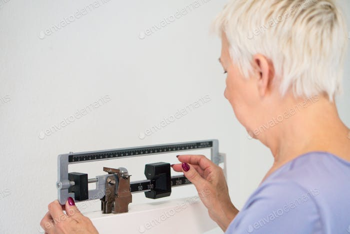 Senior adult woman weighting herself