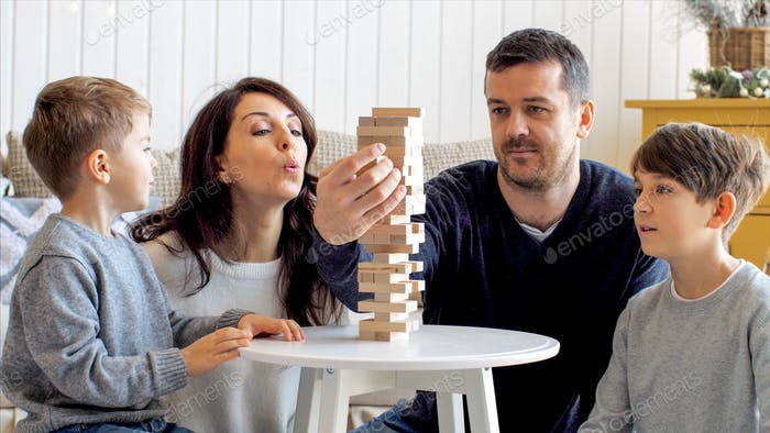 Family of four people is playing in board game with wooden tower together at home.