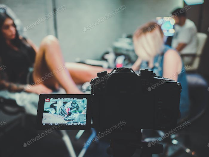 Photographer or videographer working with attractive woman tattoo artist