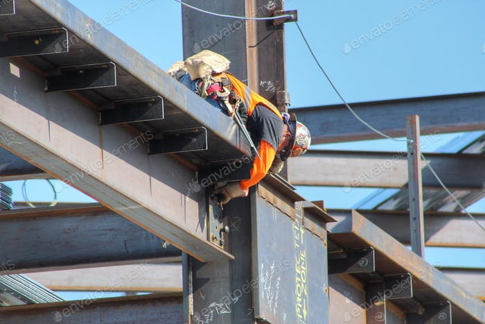 A construction worker up on a beam.