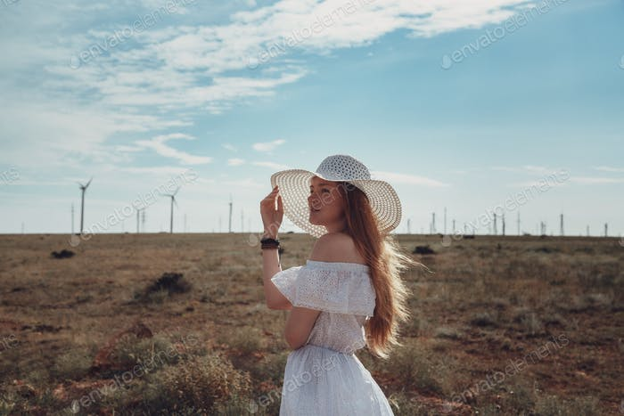 A beautiful redheaded woman in a white dress and hat on a sweltering day