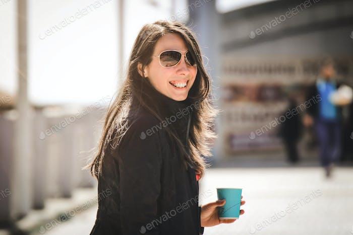 La mujer sonriente está bebiendo un café