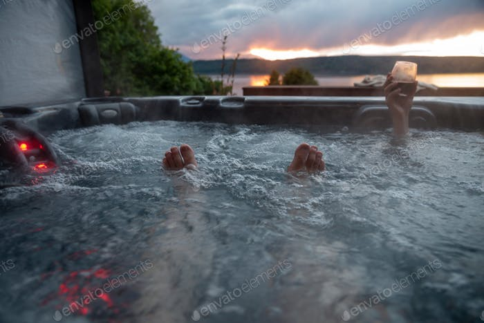 Point of view toes peeking out of hot tub bubbling water at sunset with wine in hand.