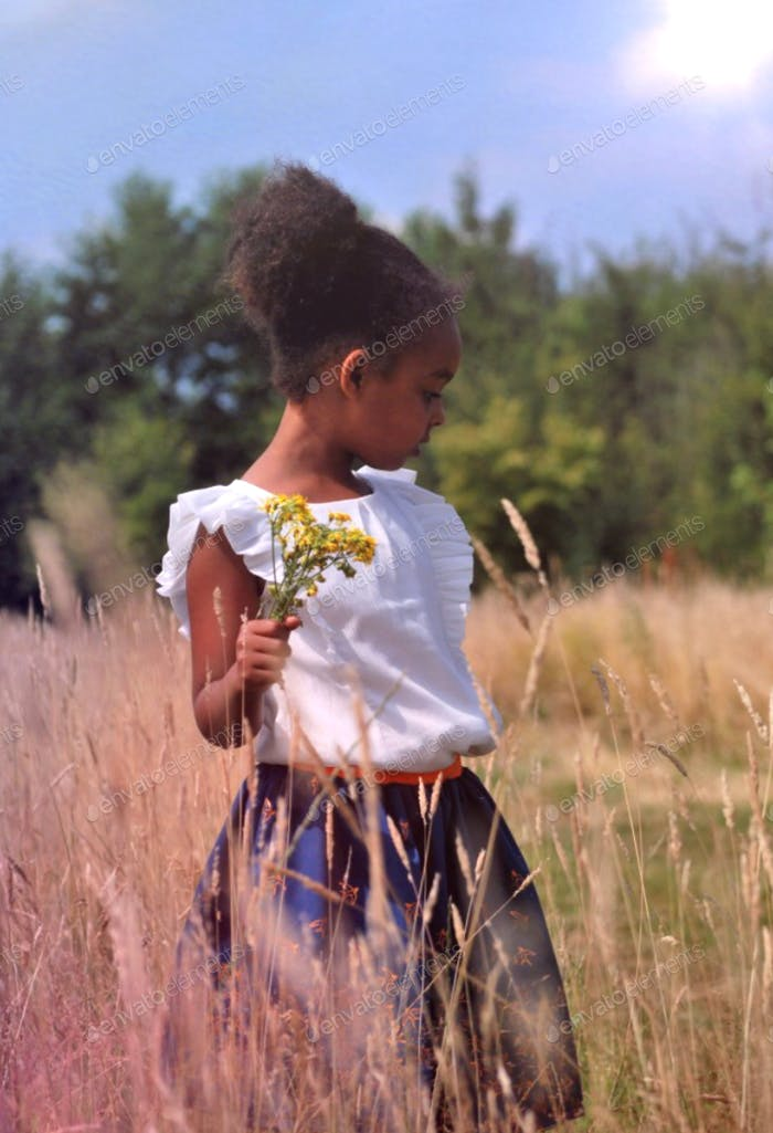 Black girl walking in a hayfield (field) picking yellow flowers during summer