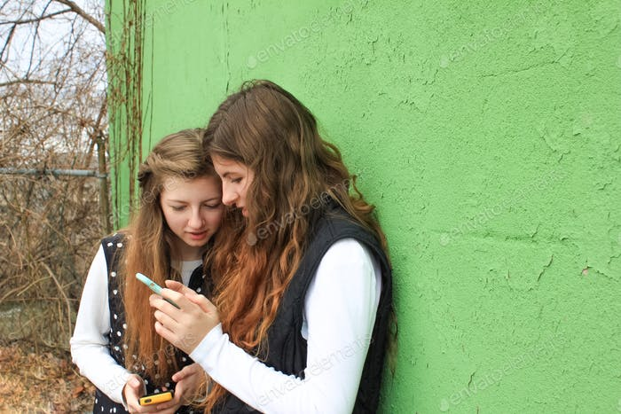 Two young women teens by green wall background using cell phones and reading social media posts