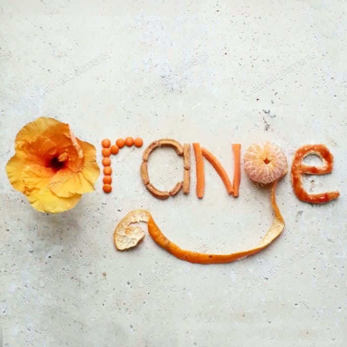 orange,creative typography made with food and flowers on stone table