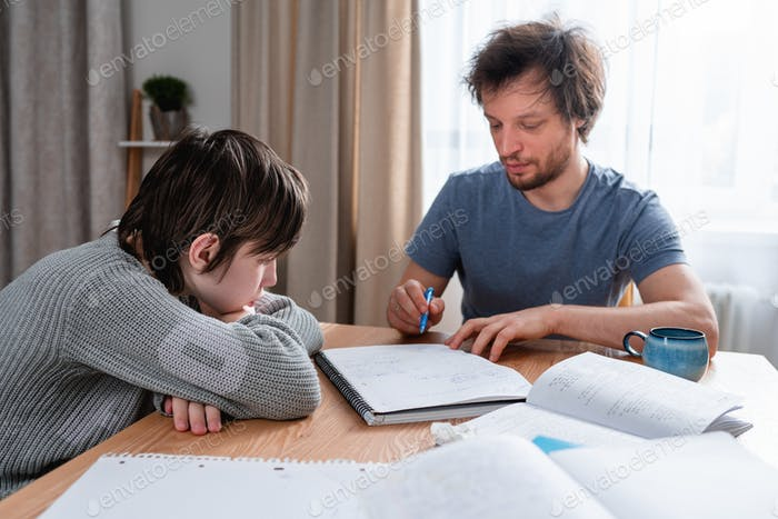 Adult man helping his son doing lessons at home during lockdown. Difficulties of home education