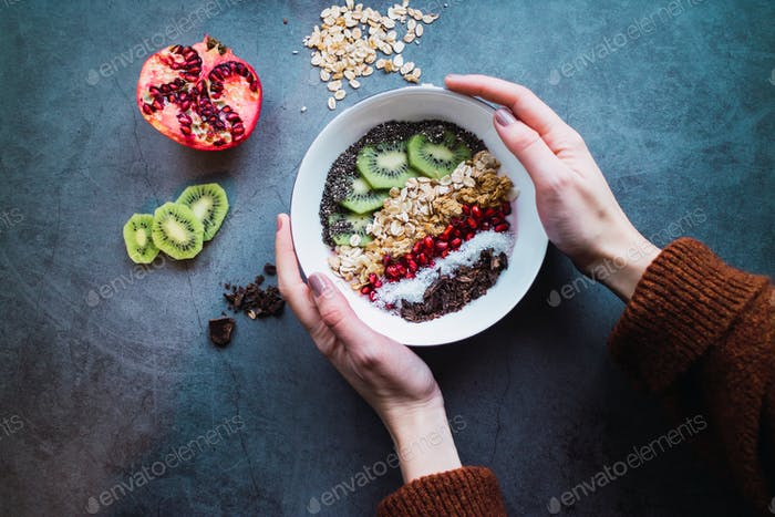 Woman's hands holding a smoothie bowl with vegan ingredients on concrete background. Healthy life. F