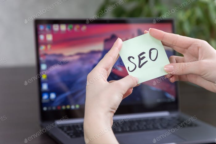 sticker with the inscription SEO in female hands on the background of a laptop