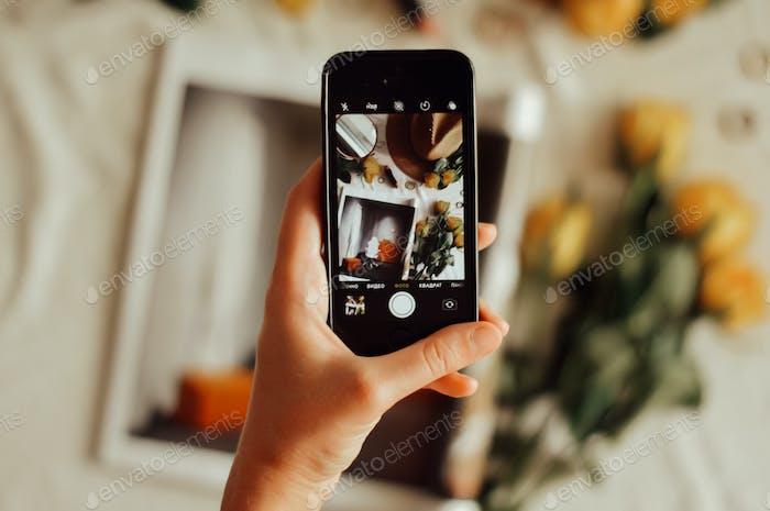 Mano sosteniendo el teléfono. Usando el teléfono. La mano de una mujer toma una foto en su teléfono.