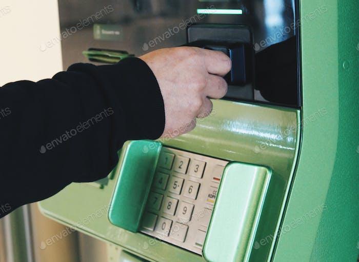 Der Mann zahlt Rechnungen über den Geldautomaten von der Kreditkarte