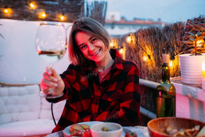 Beautiful hipster millenial girl sit on the nice terrace having dinner barbeque and drinking wine