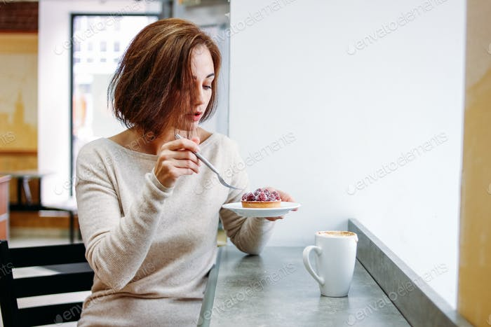 Charming brunette woman sitting at window eating dessert in cafe