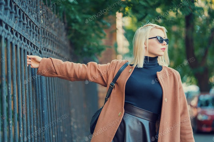 Mysterious stylish blonde girl walks through the European metropolis, holding the old fence