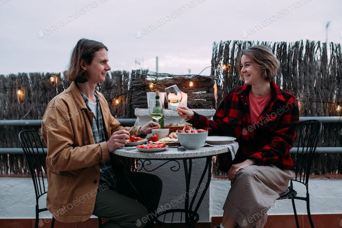 Beautiful hipster millenial couple sit on the nice terrace having dinner barbeque and drinking wine